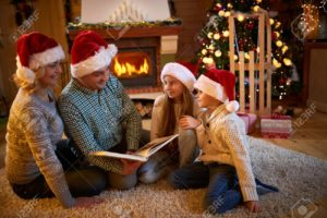 parents and children's read a book at fireplace on Christmas eve. Family with child celebrating Xmas.